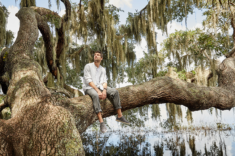 man sitting on sideway branch of a huge tree with hanging lichen