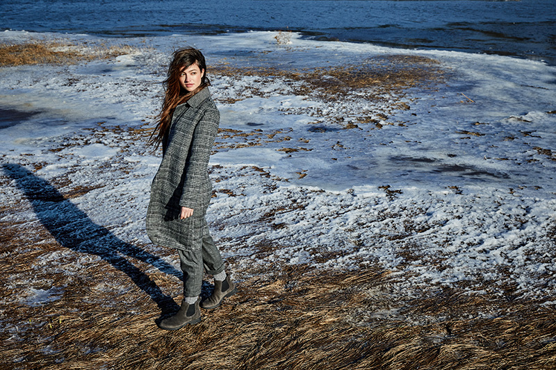 woman in gray plaid coat on white sand beach
