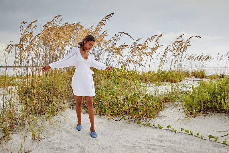 woman in white dress with blue shoes on white sand beach