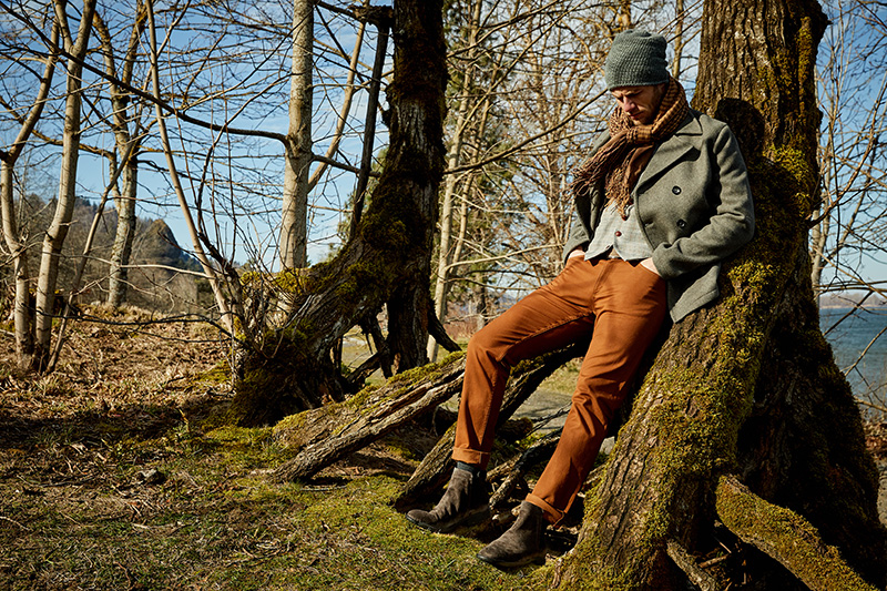 man in woods wearing brown pants, scarf and beanie
