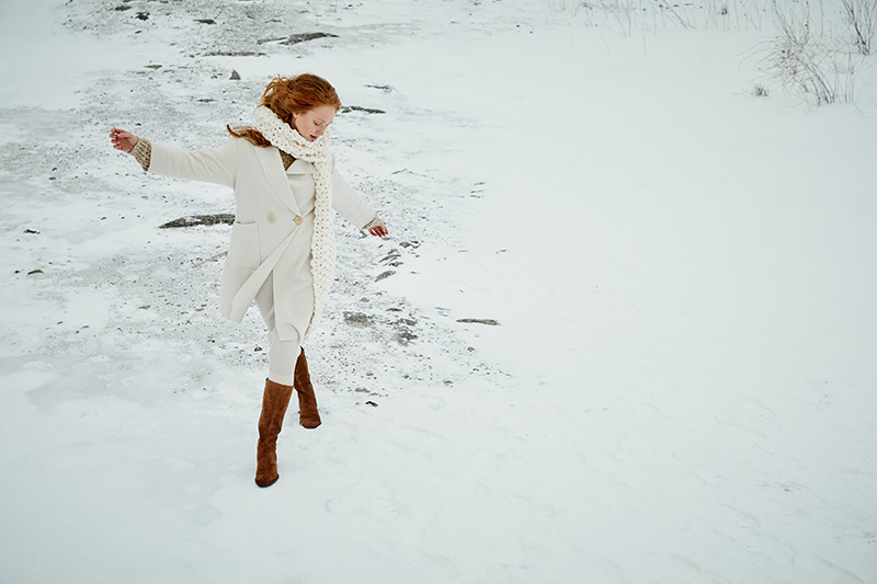 ginger woman in white coat, white scarf on snowy background