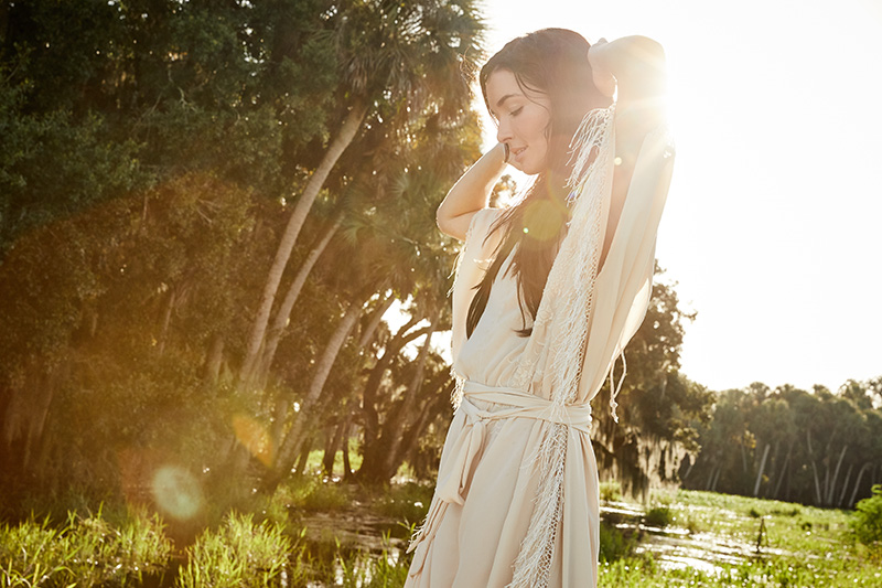 woman in white dress by marsh with bokeh
