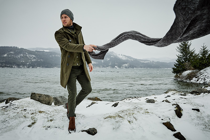 man holding long scarf on windy day