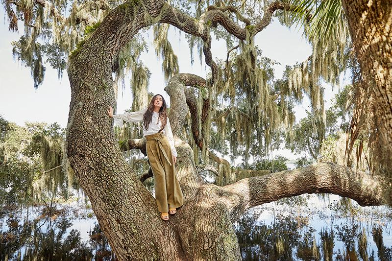 woman standing in a huge lichen-draped tree