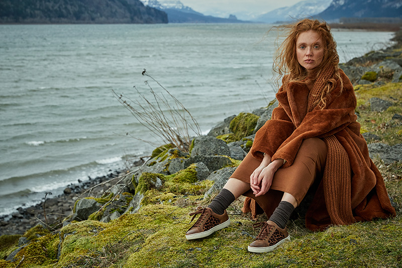 woman in brown outfit sitting on mossy shoreline
