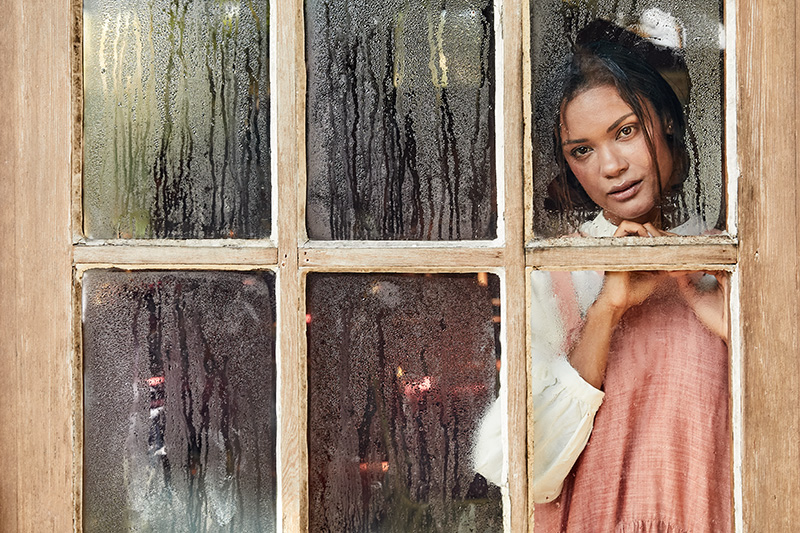 woman in pink dress looking out wet windows
