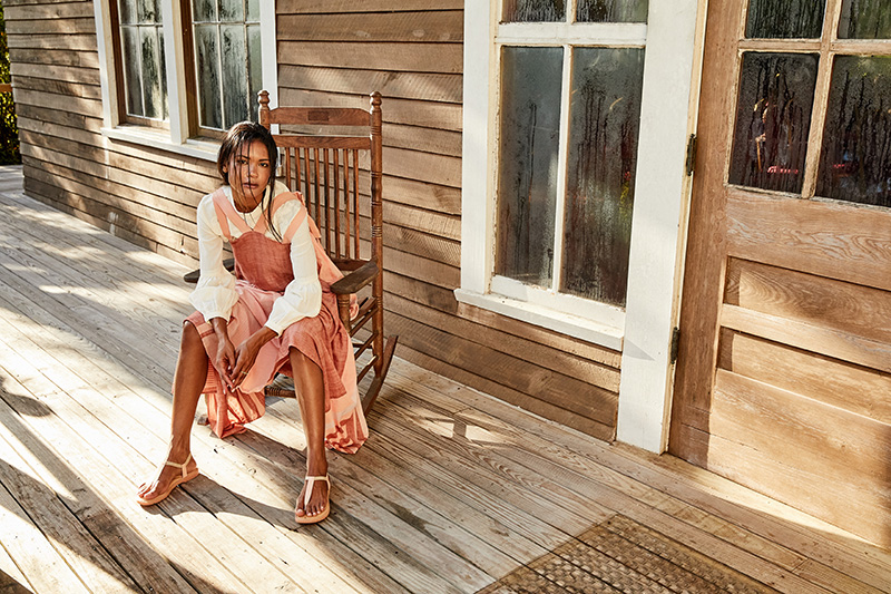 woman in pink dress sitting in porch rocking chair