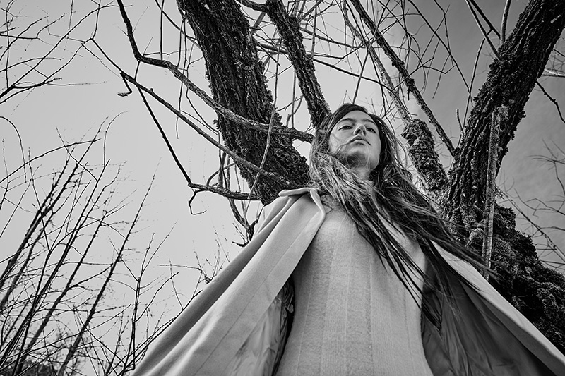 grayscale image of woman under winter trees